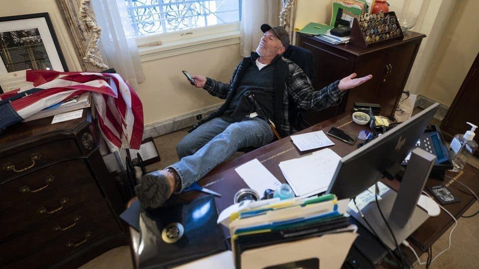 """بعد الجلوس على مكتب رئيسة مجلس النواب الأمريكي نانسي بيلوسي ، ترك أحد المتظاهرين رسالة كتب عليها """"لن نتراجع"""""""
